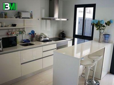 белая островная кухня с барной стойкой и каменная столешница