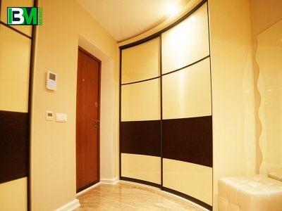 бежевый радиусный шкаф купе кремового цвета с шоколадным
